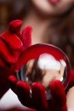 Fond de Noël avec une boule en verre brillante sur les mains modèles Chr Photos stock