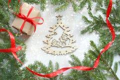Fond de Noël Cadre vert de branches d'arbre sur le fond en bois blanc, boîte-cadeau avec le ruban rouge de satin, le Christ en bo photo libre de droits