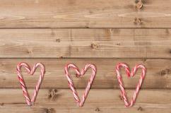 Fond de Noël Cannes de sucrerie, forme de coeur images libres de droits
