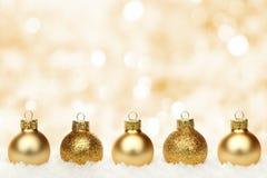 Fond de Noël d'or avec des babioles dans la neige Photographie stock
