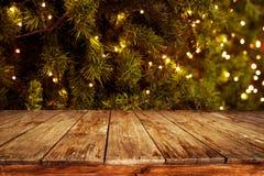 Fond de Noël et de nouvelle année avec la table en bois foncée vide de plate-forme au-dessus de l'arbre de Noël et du bokeh léger Images libres de droits