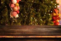 Fond de Noël et de nouvelle année avec la table en bois foncée vide de plate-forme au-dessus de l'arbre de Noël et du bokeh léger Photos libres de droits