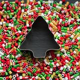 Fond de Noël Les enfants perlés faits main d'ornements peuvent faire Coupeurs orientés de biscuit de Noël sur le noir Image stock
