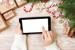 Fond de Noël : les mains femelles utilise le comprimé ouvert avec l'espace de copie sur la table en bois rustique couverte de déc image stock