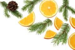 Fond de Noël orange coupée en tranches avec l'arbre de cône et de sapin d'isolement sur la vue supérieure de fond blanc Photos stock