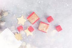Fond de Noël : paniers, boîte-cadeau et étoiles d'or sous la neige Images stock