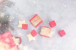 Fond de Noël : paniers, boîte-cadeau et étoiles d'or sous la neige Photo stock