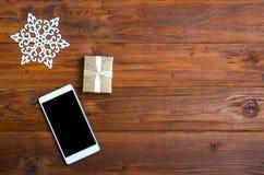 Fond de Noël : smartphone, et un cadeau sur une table en bois t image libre de droits
