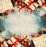 Fond de Noël avec des boîte-cadeau, des décorations de fête rouges de vacances et des flocons de neige de papier Photos stock
