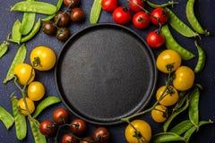 Fond de nourriture avec l'espace de copie Tomates rouges et jaunes et pois autour de plat noir epty de fonte Vue supérieure Photos stock