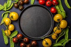 Fond de nourriture avec l'espace de copie Tomates rouges et jaunes et pois autour de plat noir epty de fonte Vue supérieure Photos libres de droits