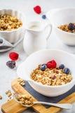 Fond de nourriture de petit déjeuner Granola avec du lait et des baies sur la table blanche photos libres de droits