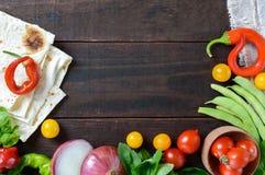 Fond de nourriture : tomates-cerises, poivre de piment, basilic, haricots verts, oignons, pain pita Photographie stock libre de droits