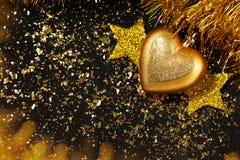 Fond de nouvelle année, étoiles d'or, boule de Noël, scintillement, table noire Images stock