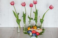 Fond de Pâques avec des oeufs de pâques et des tulipes roses dans des bouteilles en verre sur le fond en bois clair Photos libres de droits