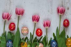 Fond de Pâques avec des oeufs de pâques et des tulipes roses sur l'herbe verte Photos libres de droits