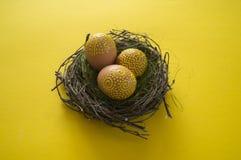 Fond de Pâques avec les oeufs jaunes dans le nid sur la table photographie stock