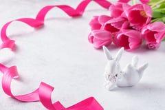 Fond de Pâques avec les tulipes roses et le lapin mignon photographie stock libre de droits