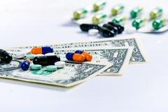 Fond de pharmacie Pilules sur un billet de banque d'isolement sur un fond blanc Différents types de capsules sur le billet de ban Image libre de droits
