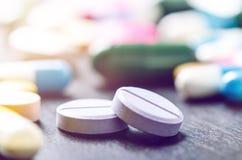 Fond de pharmacie sur une table noire Comprimés sur un fond noir Pillules Médecine et sain Fermez-vous vers le haut des capsules  Photographie stock libre de droits