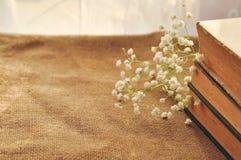 Fond de ressort de cru avec les fleurs blanches, vieux livres jaunis sur la toile de jute closeup photos stock
