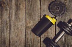 Fond de séance d'entraînement de forme physique Haltères sur le plancher ou la table en bois de gymnase images stock