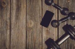 Fond de séance d'entraînement de forme physique Haltères sur le plancher ou la table en bois de gymnase photos libres de droits