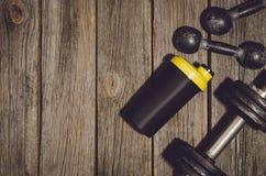Fond de séance d'entraînement de forme physique Haltères sur le plancher ou la table en bois de gymnase Photographie stock