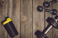 Fond de séance d'entraînement de forme physique Haltères sur le plancher ou la table en bois de gymnase Photographie stock libre de droits