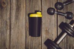 Fond de séance d'entraînement de forme physique Haltères sur le plancher ou la table en bois de gymnase photos stock