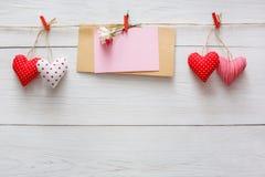 Fond de Saint Valentin, coeurs d'oreiller et carte sur le bois Images stock