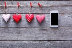 Fond de Saint Valentin, coeurs d'oreiller et smartphone sur le bois Photos stock