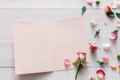 Fond de Saint Valentin, fleurs roses et carte sur le bois blanc Images libres de droits