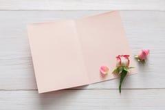 Fond de Saint Valentin, fleurs roses et carte sur le bois blanc Photo libre de droits