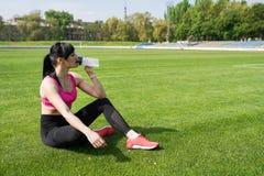 Fond de sport avec l'espace de copie L'athl?te de femme fait une pause, elle eau potable, sur une course un jour chaud Concept de photos libres de droits