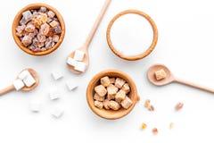 Fond de sucre sur le blanc Cuvettes avec différents genres de sucre Vue supérieure photos stock