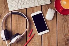 Fond de table de bureau avec le smartphone, les écouteurs et le clavier d'ordinateur Concept de lieu de travail ou d'espace de tr Photos stock