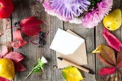 Fond de thanksgiving avec les fruits, les fleurs, la carte de voeux et l'enveloppe saisonniers sur une table en bois rustique Con Images stock