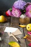 Fond de thanksgiving avec les fruits, les fleurs, la carte de voeux et l'enveloppe saisonniers sur une table en bois rustique Con Images libres de droits