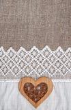 Fond de toile de jute avec le tissu de dentelle et le coeur en bois Photographie stock libre de droits