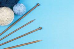 Fond de tricotage Aiguilles de tricotage et boules de fil coloré sur le fond bleu Images stock