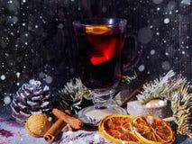 Fond de vacances avec des verres de vin rouge, de vin rouge et d'ornements de Noël sur la table en bois Images stock