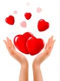 Fond de vacances avec deux mains et coeurs rouges. Photographie stock