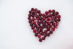 Fond de vacances Coeur des cerises rouges surgelées sur un fond blanc de neige photos stock