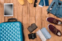 Fond de vacances d'été avec des accessoires de voyage bagage fermé, chaussures, dispositifs numériques et passeports Photographie stock