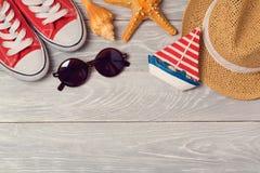 Fond de vacances d'été avec des chaussures, des lunettes de soleil et le chapeau sur le conseil en bois Photographie stock