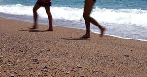 Fond de vacances d'été avec deux jeunes hommes marchant sur la plage - échouez la vidéo des milieux 4k de voyage de vacances banque de vidéos