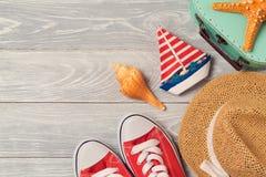 Fond de vacances d'été avec les chaussures, le bateau et le chapeau sur le conseil en bois Photos libres de droits