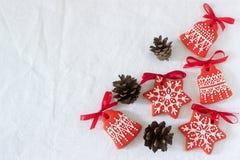 Fond de vacances de nouvelle année de Noël, biscuits rouges de pain d'épice et cônes sur la table blanche Copiez l'espace Images libres de droits