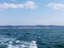 Fond de vague d'été de surface de la Mer Noire Vue de yacht Paysage marin exotique avec les nuages et la ville sur l'horizon Tran images libres de droits